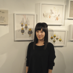 Andrea Kang posing in front of her works at My Plastic Heart. Photo taken by Stephane Bonneaud and provided by Kang herself