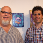 Robert Lumino, owner of Sub-Urban Vinyl, posing with Ketner and the painting he purchased